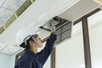 Air conditioner cleaning. Man in gloves checks the filter. Young Man Adjusting Air Conditioning System.